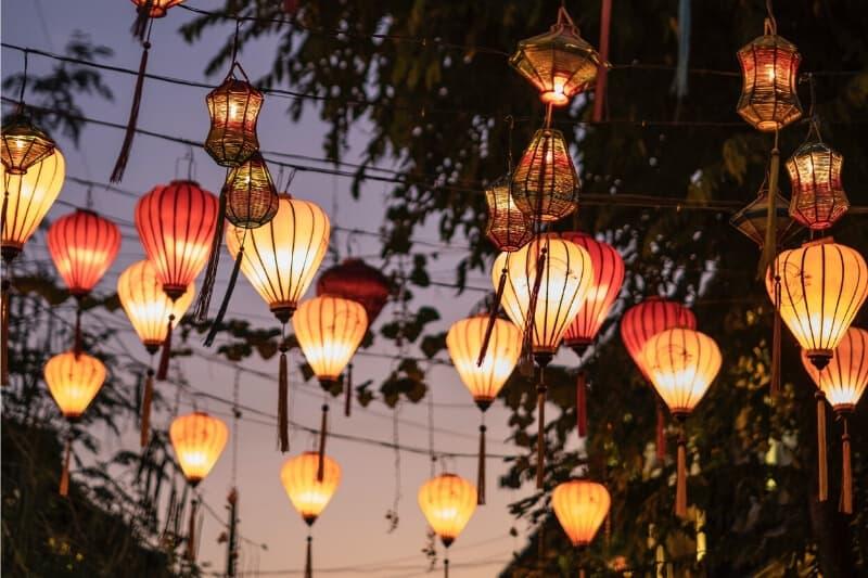 Lanterns strung above a street at dusk.