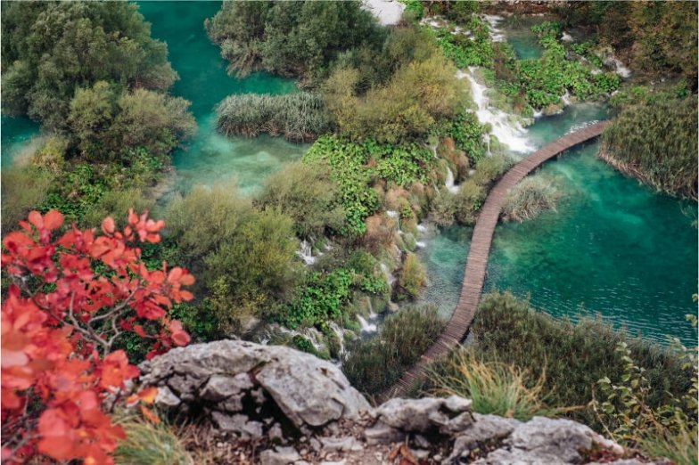A single boardwalk path winds through a landscape of rivers and waterfalls in Plitvice National Park, Croatia.