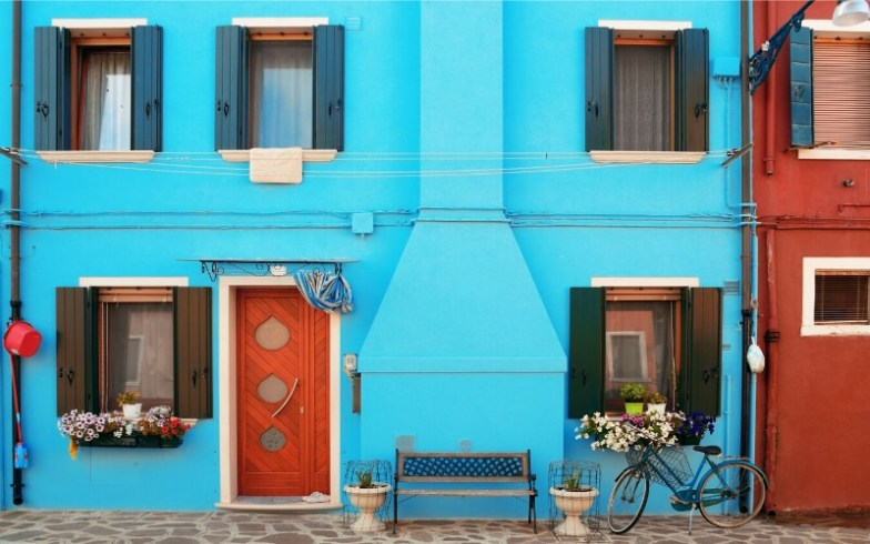 A bicycle parked in front of a bright blue house in Burano, Italy.