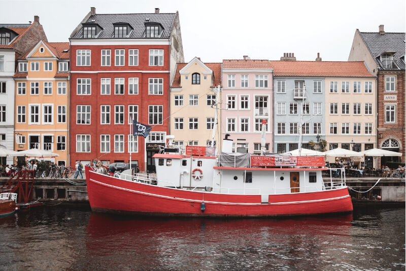 A red boat in front of a row of colourful houses in Copenhagen, Denmark.