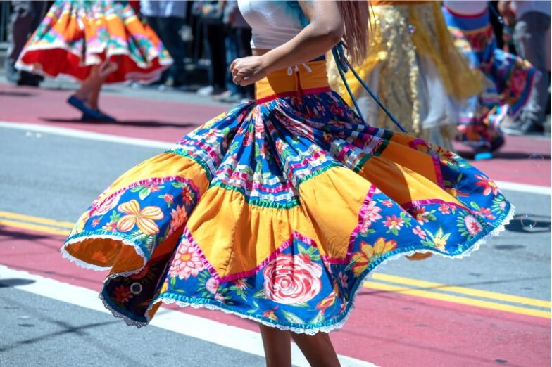 A woman twirls a brightly coloured skirt at a street festival in Mexico.