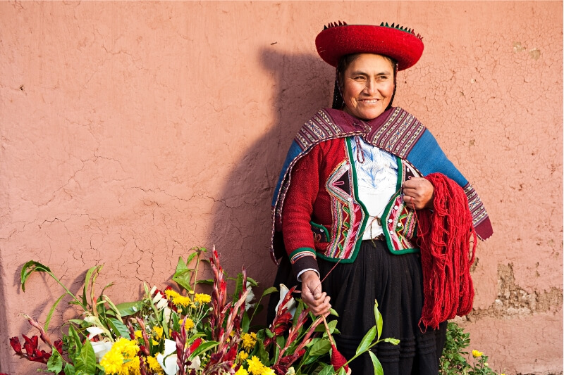 A woman sells flowers at a village market in Peru.