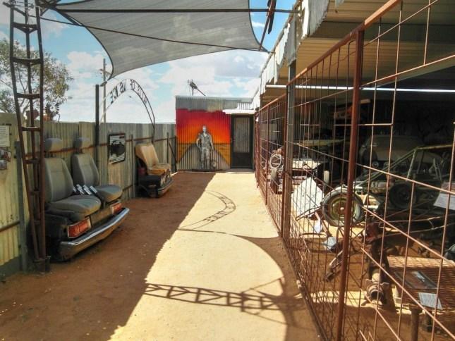 Auf dem Hof führt ein schmaler Gang einen Zaun entlang hinter dem alle Fahrzeuge ausgestellt sind