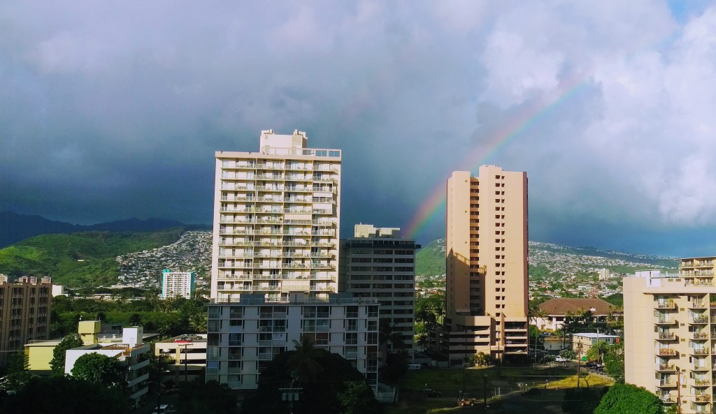 Rainbow behind hotel blocks in Honolulu Hawaii