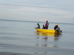Locals on sampan boat at Tg. Aru Beach in the waters of South China Sea