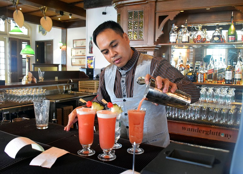 Bartender at the Long Bar pours a Singapore Sling