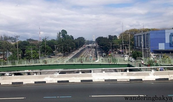 Quezon Avenue from the MRT train window. The tall white structure at the far end of the photo is the Quezon Memorial