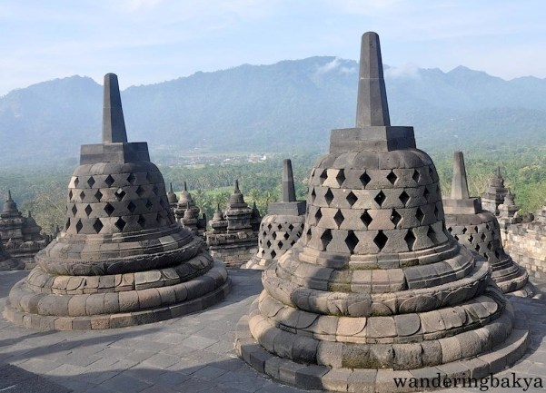 More perforated stupa. From the upper levels of Borobudur temple, the hills  and the verdant surrounding are visible.