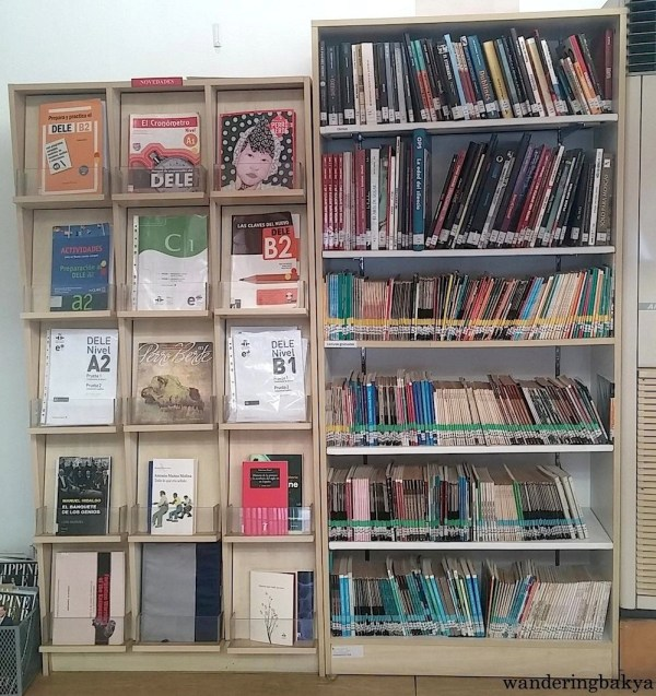 Issues of Perro Berde mingle with DELE reviewers on the left shelf. The right shelf is filled with books and comics.