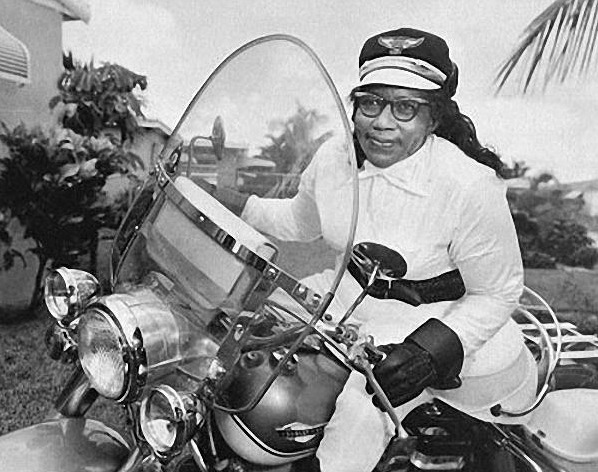 Black and white image of Bessie sitting on her Harley motorcycle, looking off in the distance with slight smile.