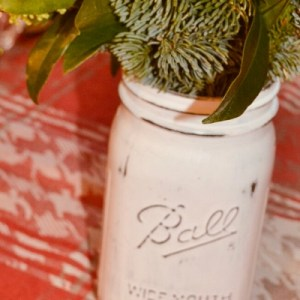 Simply white chalk painted mason jars can be one of the most useful rustic centrepiece. Create a mason jar farmhouse decoration in only a few minutes! Change the greenery to match any season, holiday, or colour scheme.