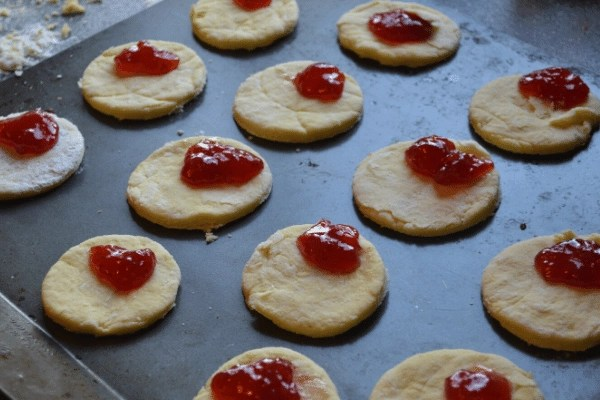 scones with strawberry jam on cookie sheet