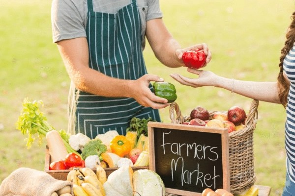 farmers market image, man selling fresh produce handing peppers to a girl