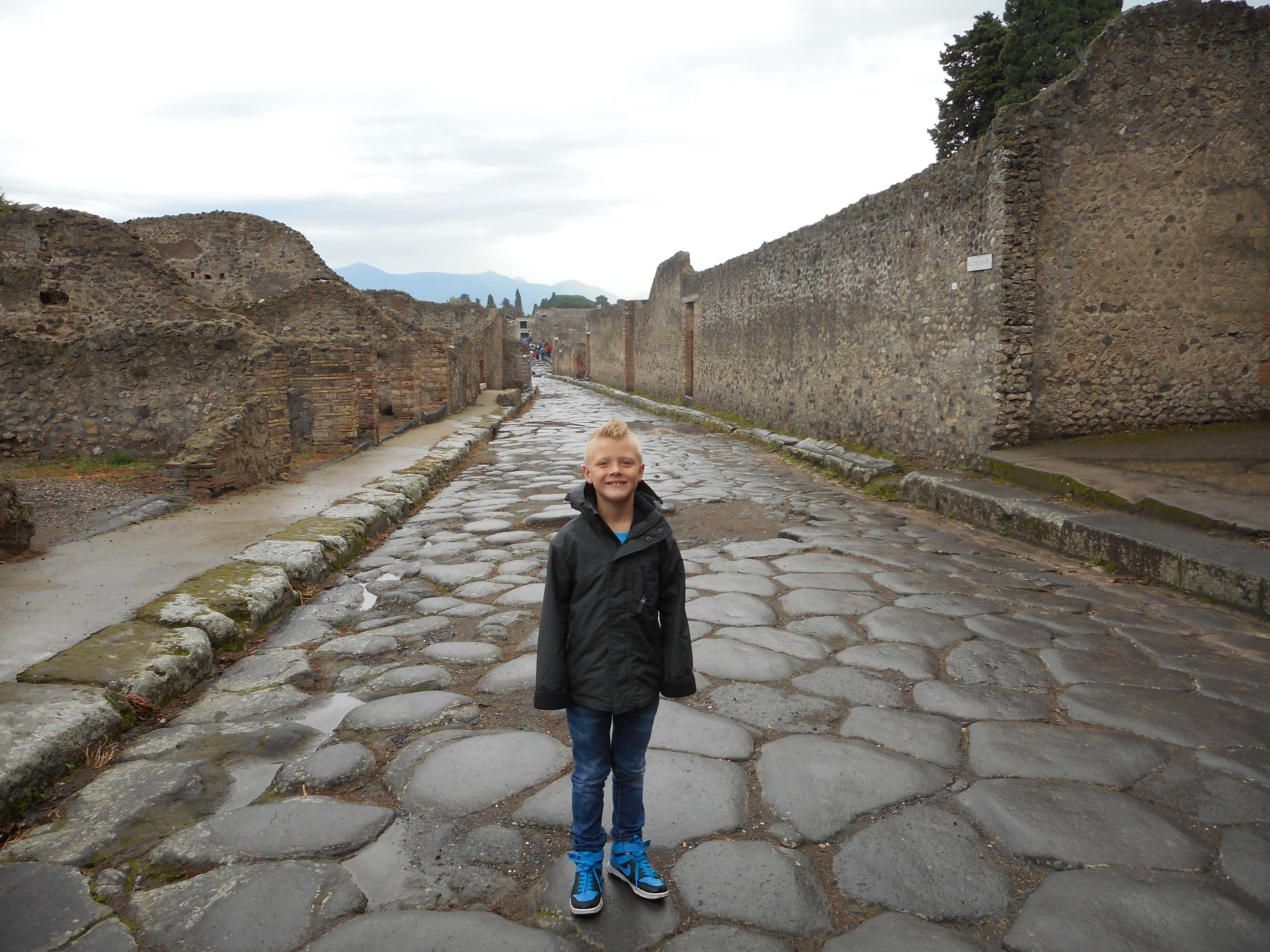 Aiden standing on the stone lined street and posing for a picture among the ruins of Pompeii.