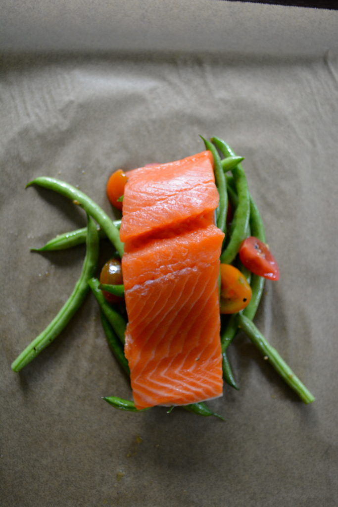 Salmon en Papillote - salmon filet on top of pile of green beans and tomatoes