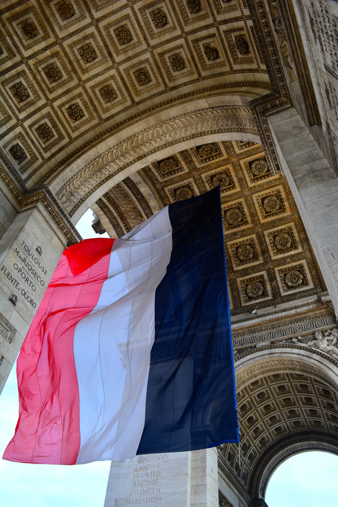 Comprehensive Guide to Paris:  French flag hanging from the Arc de Triomphe