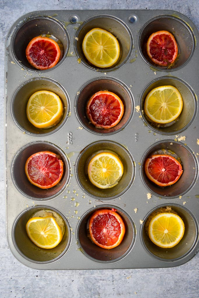 Greased muffin tin with butter, brown sugar and meyer lemon and blood orange slices