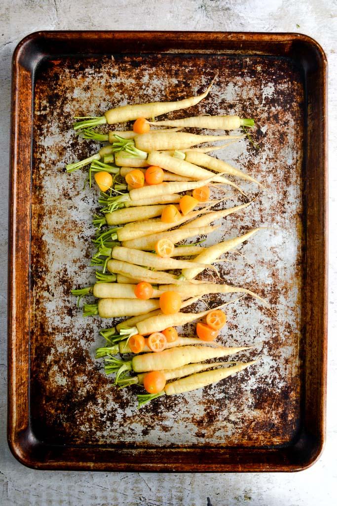 Baby carrots and halved kumquats ready to roast