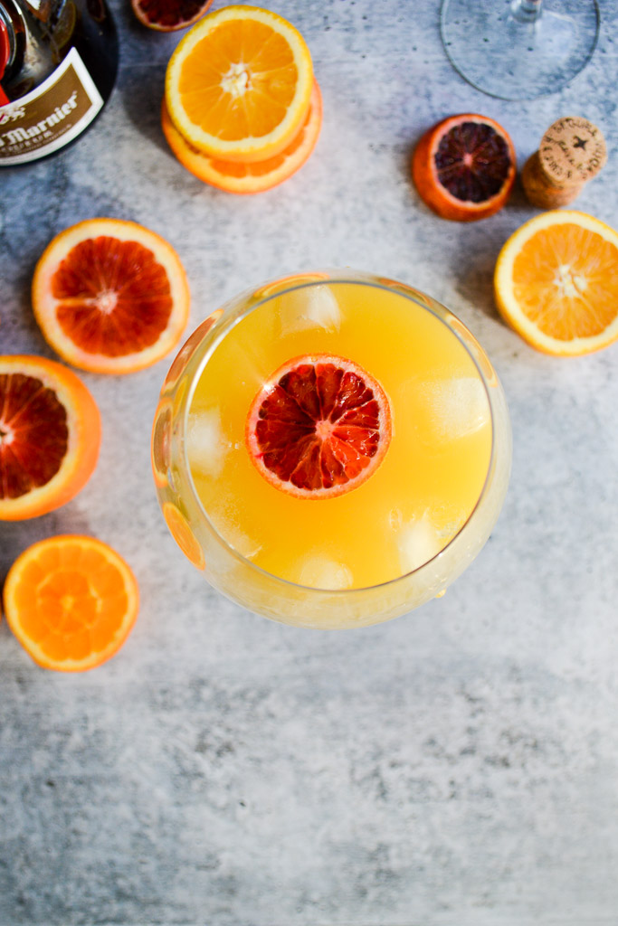 Glass of Agua de Valencia with navel oranges, blood oranges, and cara cara oranges