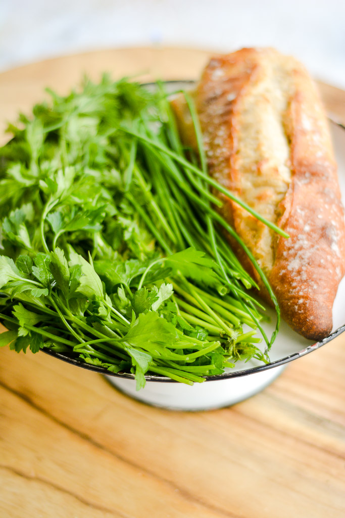 Carrot tops, parsley, chives, and french baguette