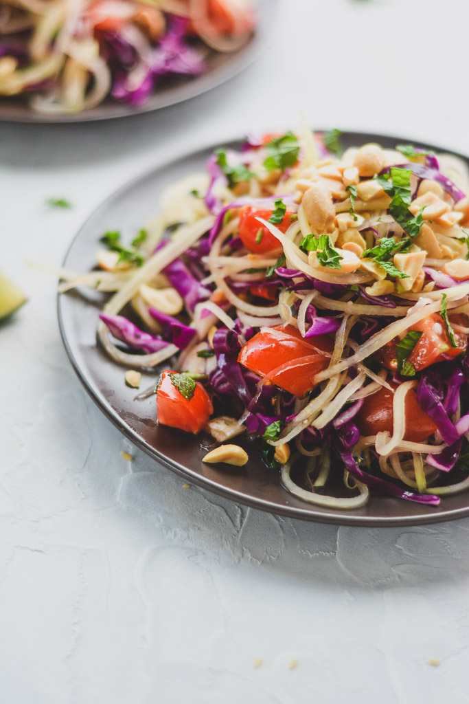 Green papaya salad with red cabbage, tomatoes, and fresh herbs