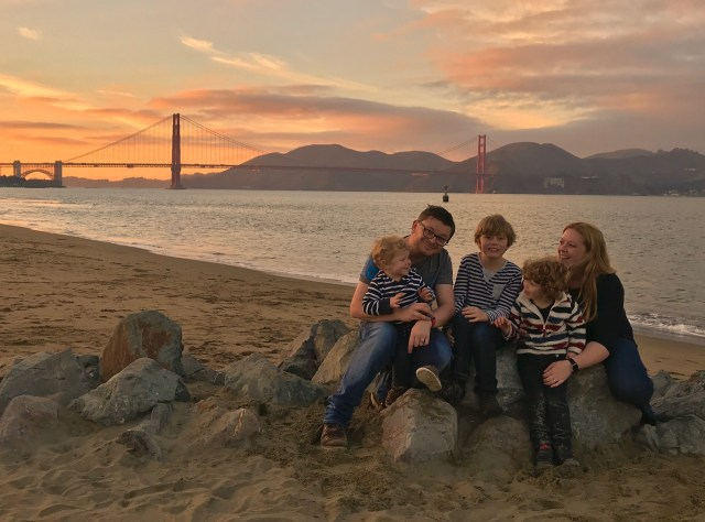 Our family sitting in front of the Golden Gate bridge in San Francisco during a beautiful sunset.