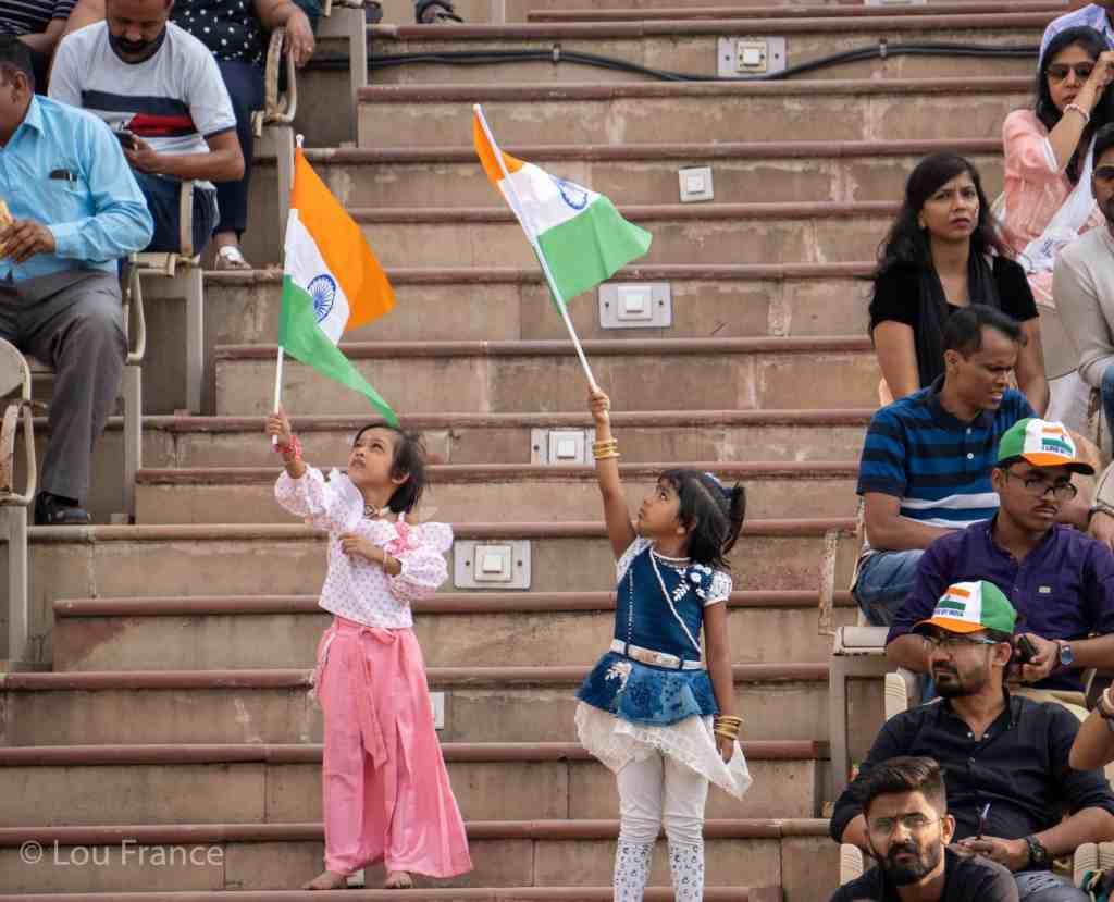 Two young girls wave Indian flags at the ceremony stadium