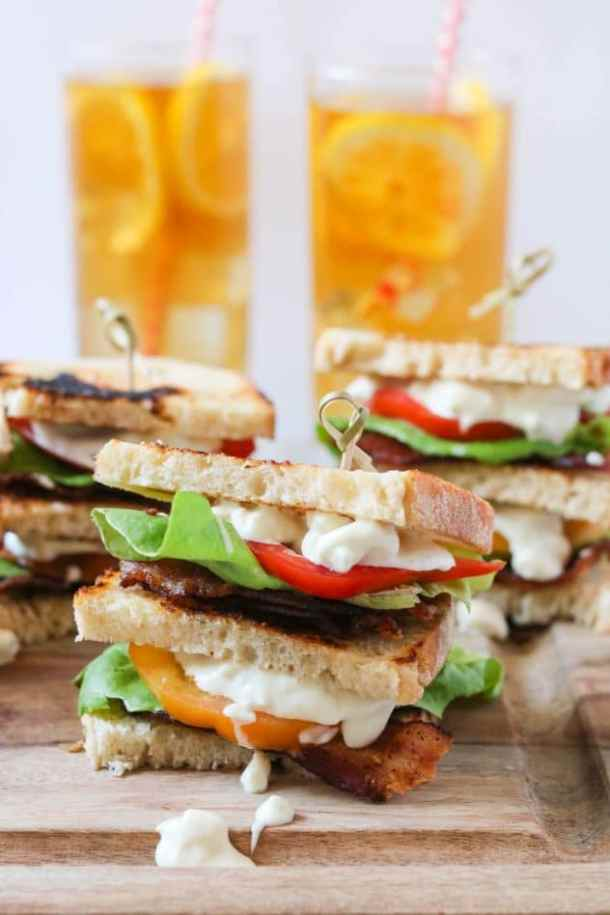 BLT club sandwich with blue cheese mayo and glasses of iced tea in the background