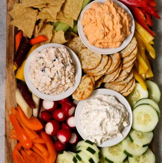a party platter with fresh vegetables and chips and three varieties of the NEW PHILADELPHIA dips
