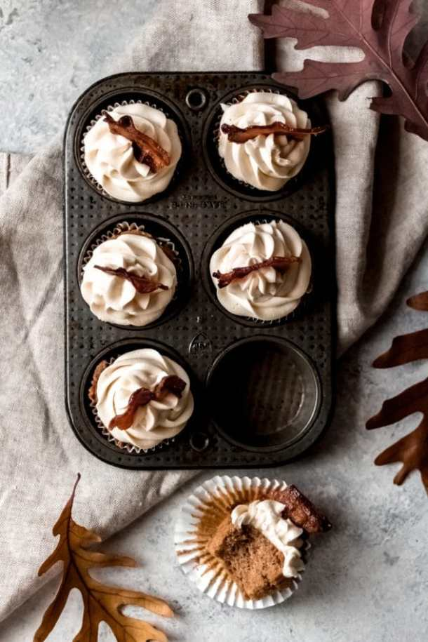 5 maple bacon spice cupcakes in a cupcake tin with one cupcake out on the table with a bite taken out of it. Fall leaves lay around the cupcakes on the table and there's a linen towel draped underneath the muffin tin.