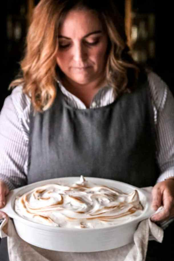 a woman holding a dish of meringue-topped sweet potato casserole