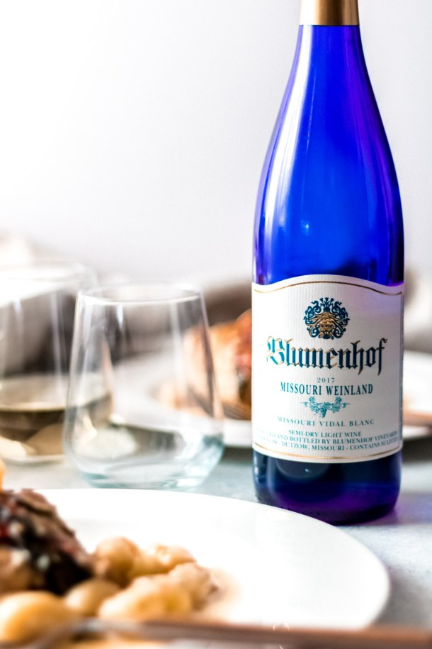 A blue bottle of Missouri Weinland vidal blanc wine with an empty wine glass to the left