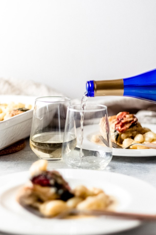 someone pouring a white missouri wine - Missouri Weinland Vidal Blanc into a wine tumbler. there is a plate of baked chicken gnocchi in the background