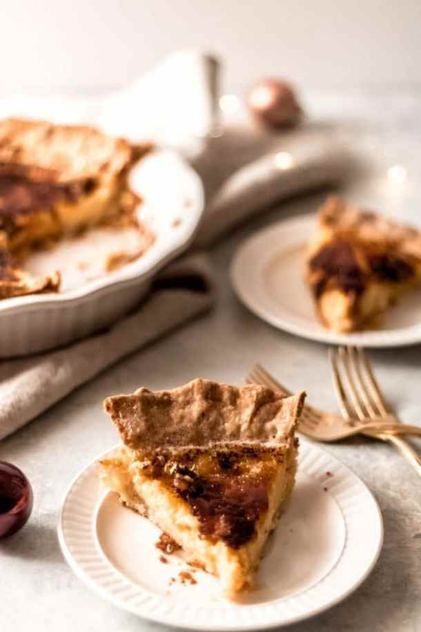 two slices of bruleed eggnog custard pie on small white plates with gold forks with the bruleed eggnog custard pie sitting in the background