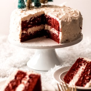 A red velvet cake with two layers on a white cake stand. Two slices have been cut out and served onto plates. Two gold forks sit next to the plates. There are tiny green and gold bottle brush trees on top of the cake and white lights glisten in the background.