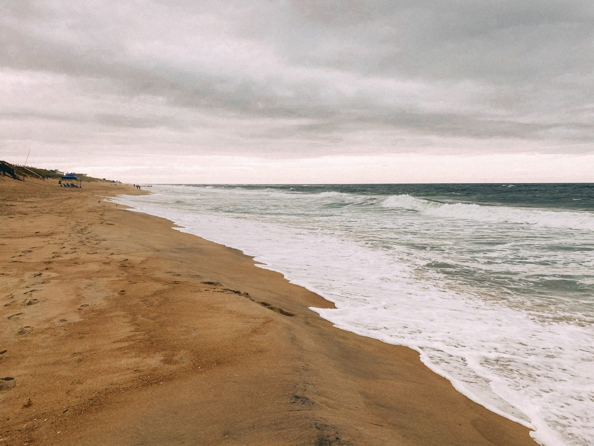 Moody skies over a damp beach and rough ocean water