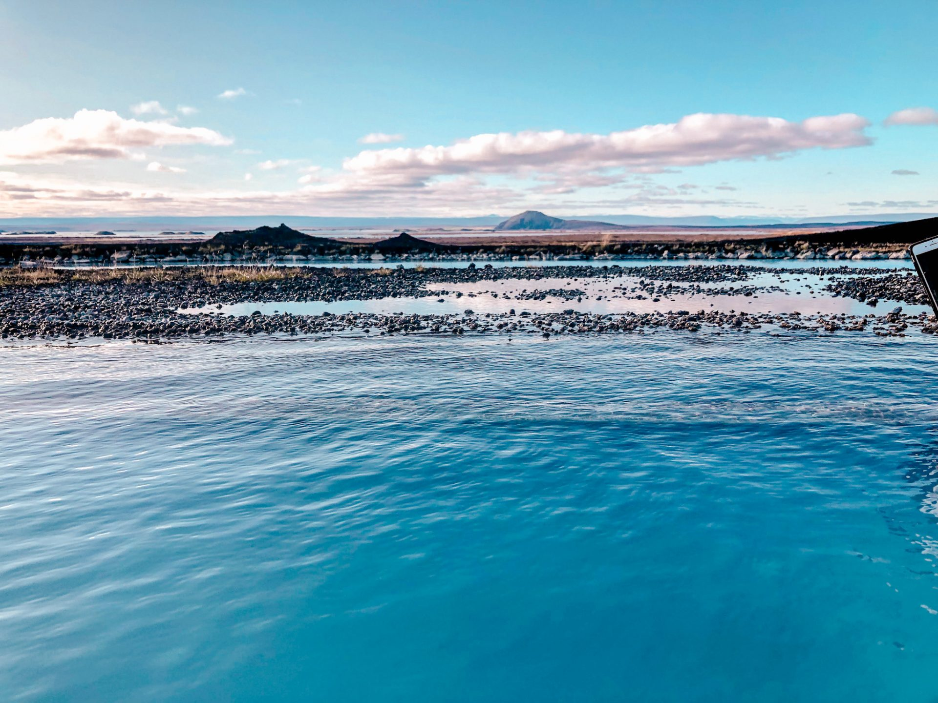 Blue sky with fluffy white clouds above a lava field located in Iceland and a geothermal pool overlooking the rolling hills.