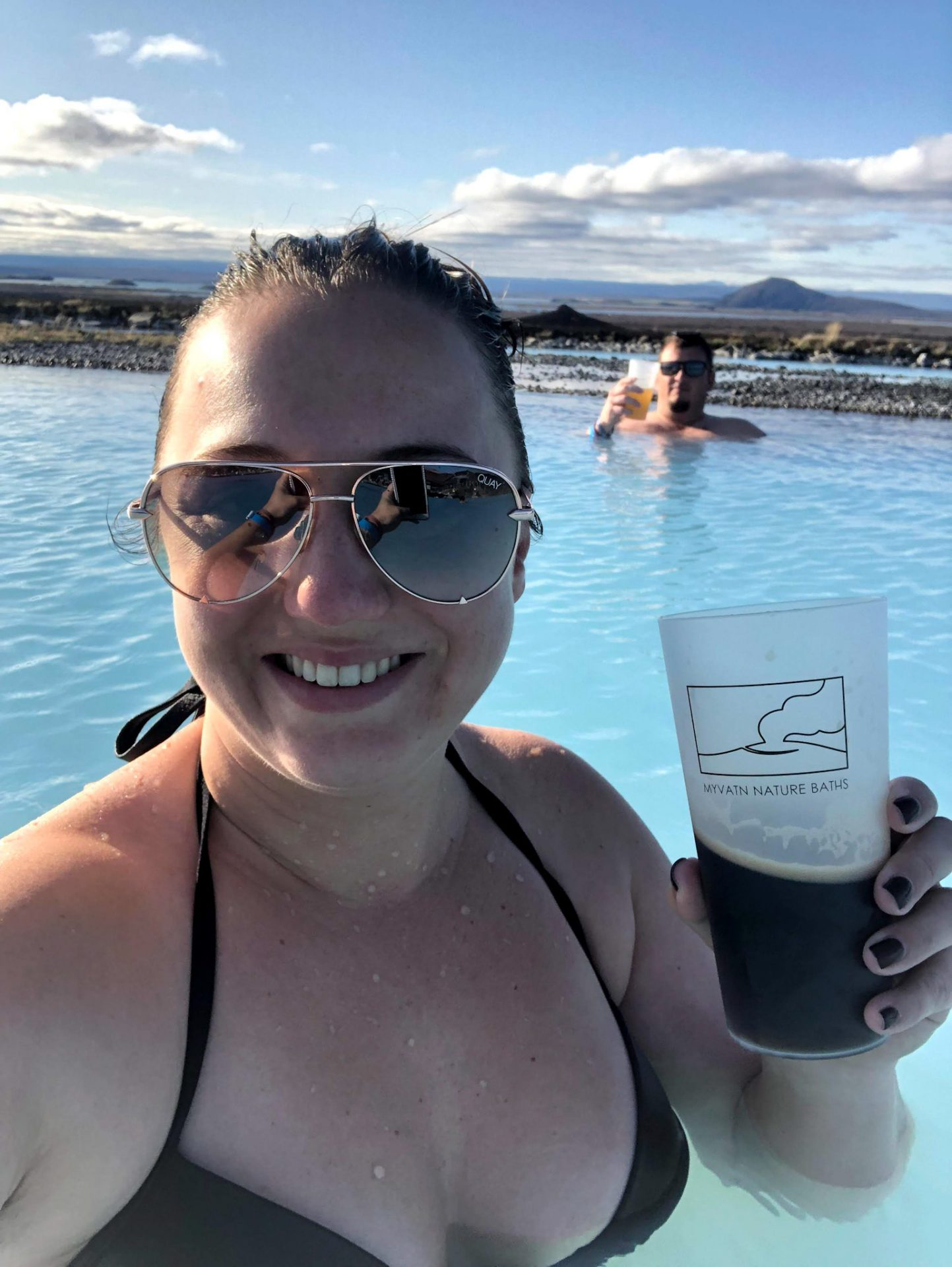 Woman in  light blue geo thermal bath experience while in Iceland. She/her wearing a black swimsuit and sunglasses holding a dark beer and smiling. In the distance her husband (he/him) wearing sunglasses and relaxing in the water with a golden beer.
