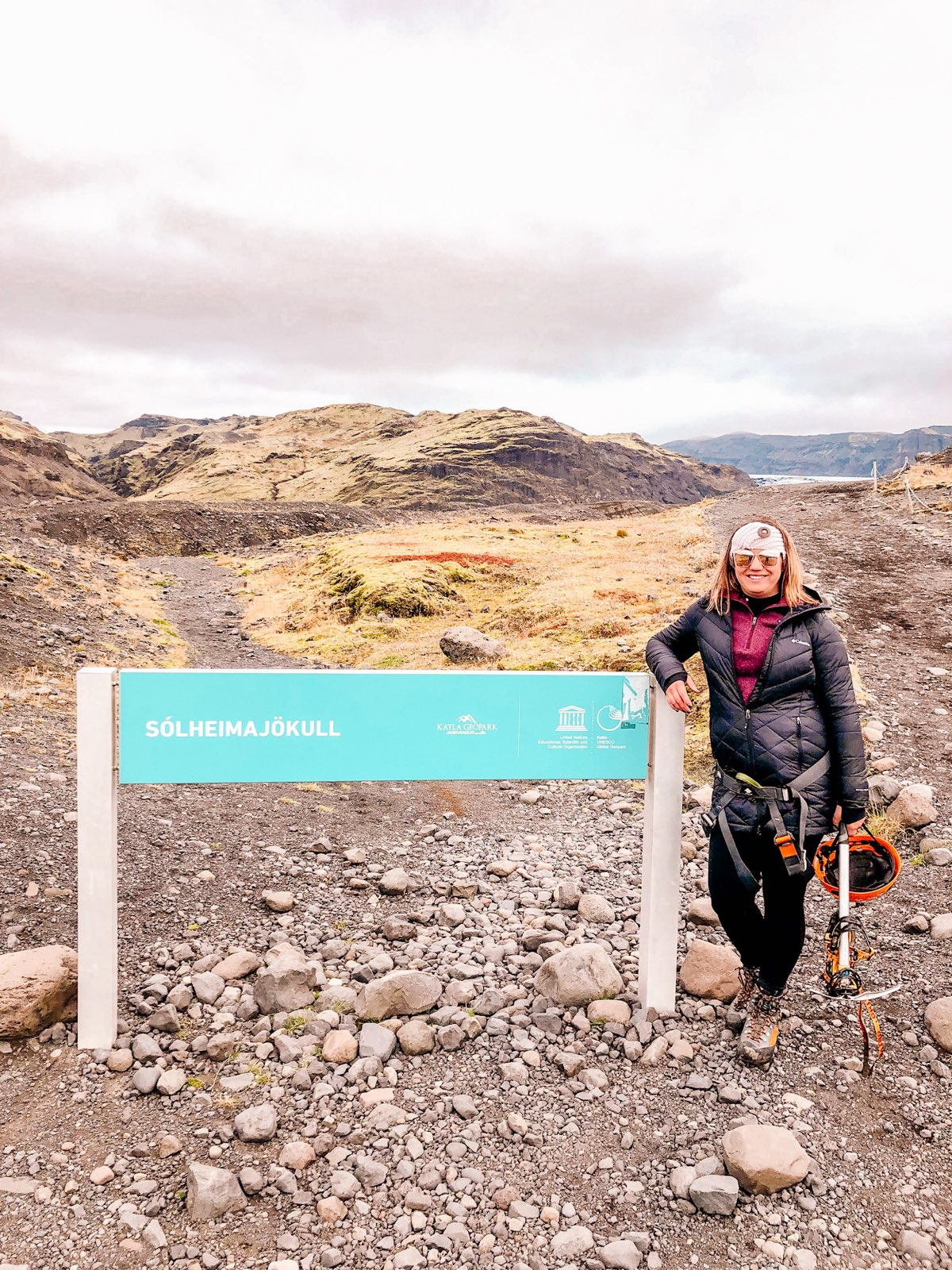 Woman next to sign stating Solheimajokull glacier. Wearing hiking boots carrying a helmet & pick axe prior to a hike on a glacier in Iceland. Wearing sunglasses, fleece & a puffer jacket.