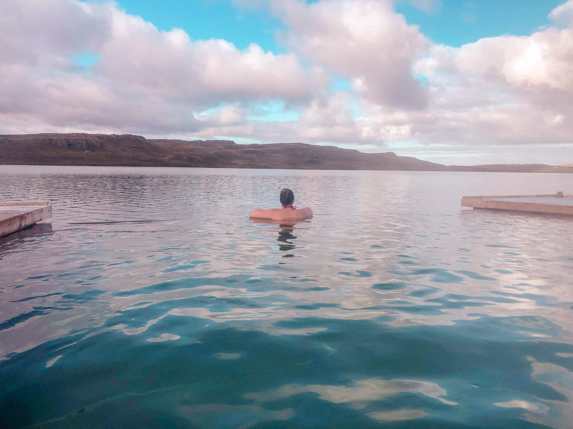 Woman (she/her) back facing the camera relaxing looking out from the geothermal pool Vok baths in Iceland out over the Lake. A blue sky overhead with huge white fluffy clouds.