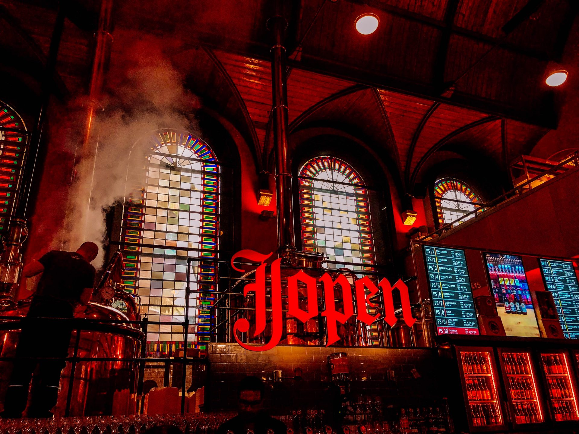 Colorful stained glass windows in the background, shiny beer vessels a top a bar area showing a lit in red sign saying Jopen with beer taps below at a beer tap room in Haarlem Netherlands Europe.