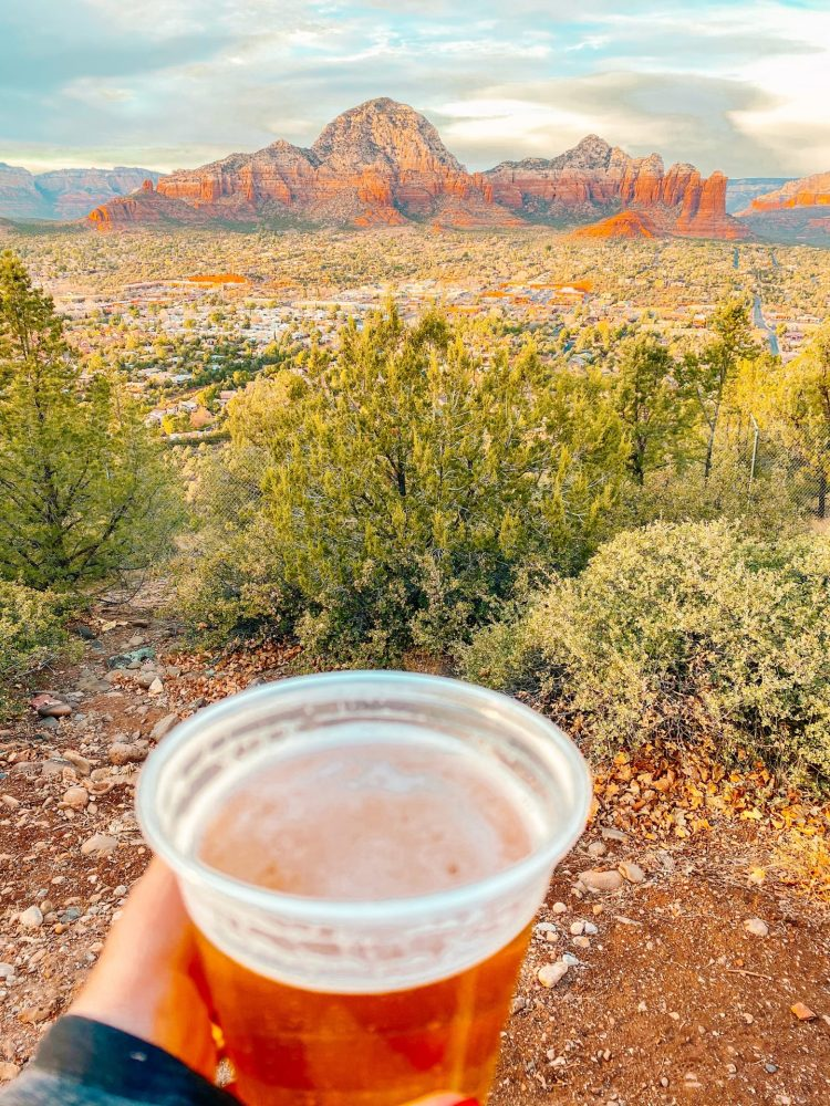 Happy Hour beer holding out a glass while looking out over the city of Sedona and the red rocks at a distance in the evening.