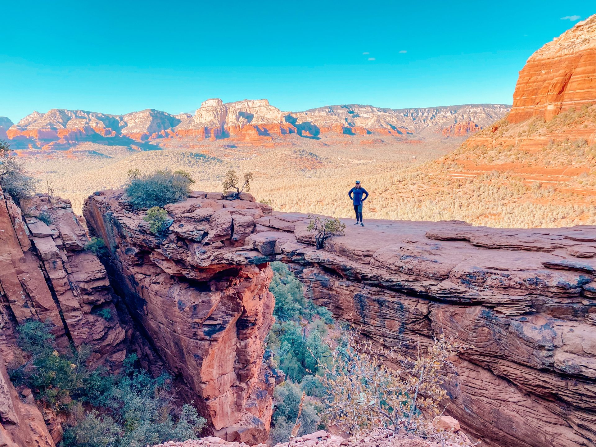 Woman standing out on the narrow bridge in Sedona Arizona known as Devils Bridge. Other red rock formations are in the distance with a blue cloudless sky overhead.