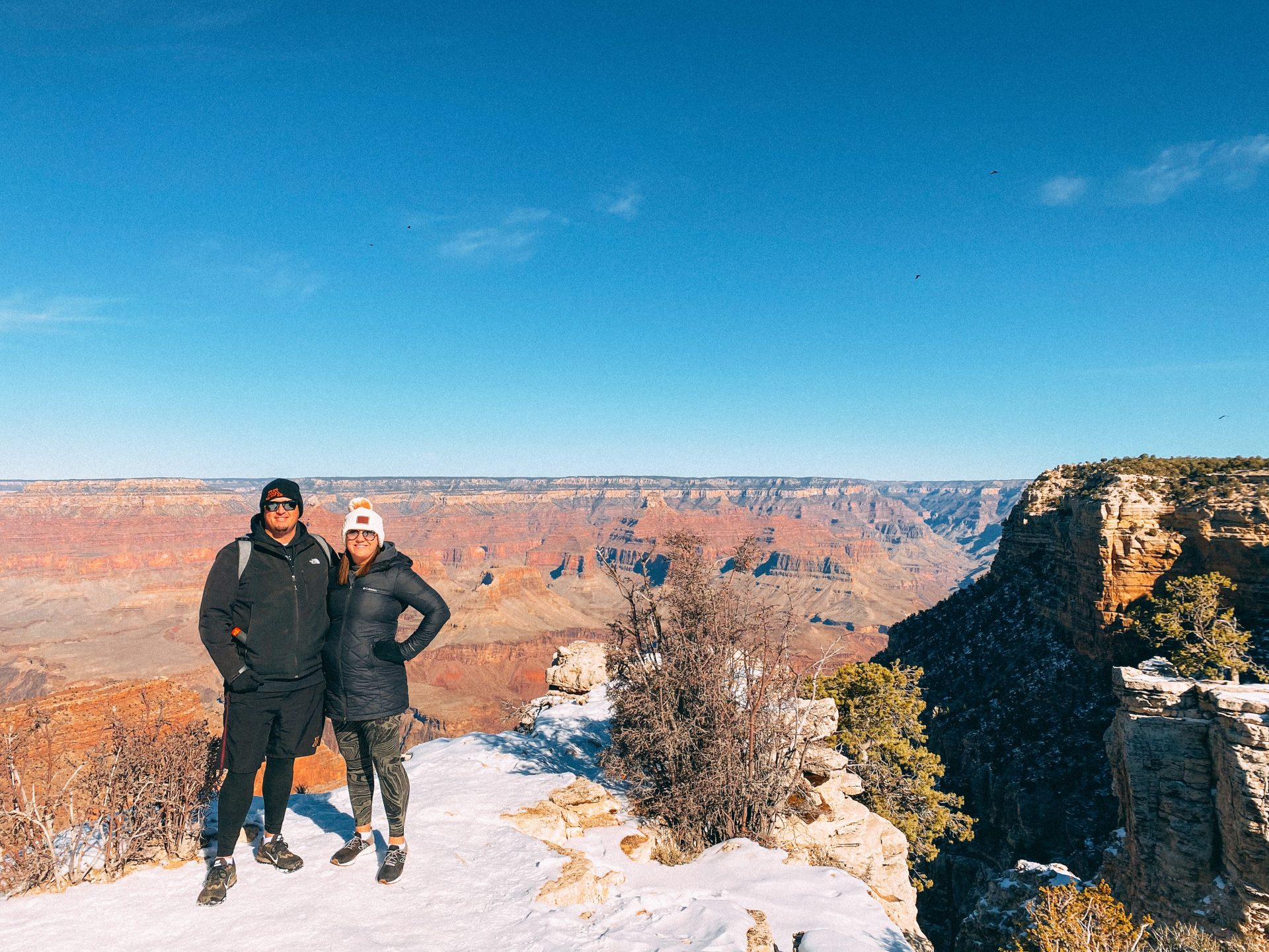 Man and woman smiling at the camera with the Grand Canyon, some shrubbery and snow in the frame.