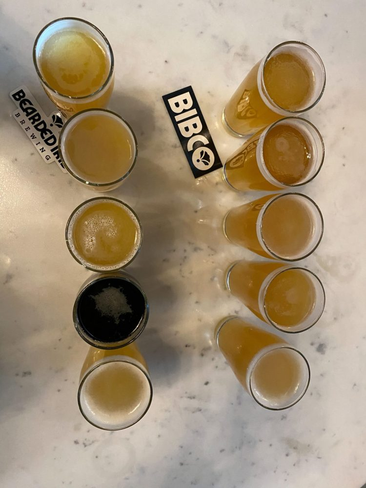 Flight of yellow colored beers and one dark beer sitting on a table at bearded iris brewing company in Nashville Tennessee.