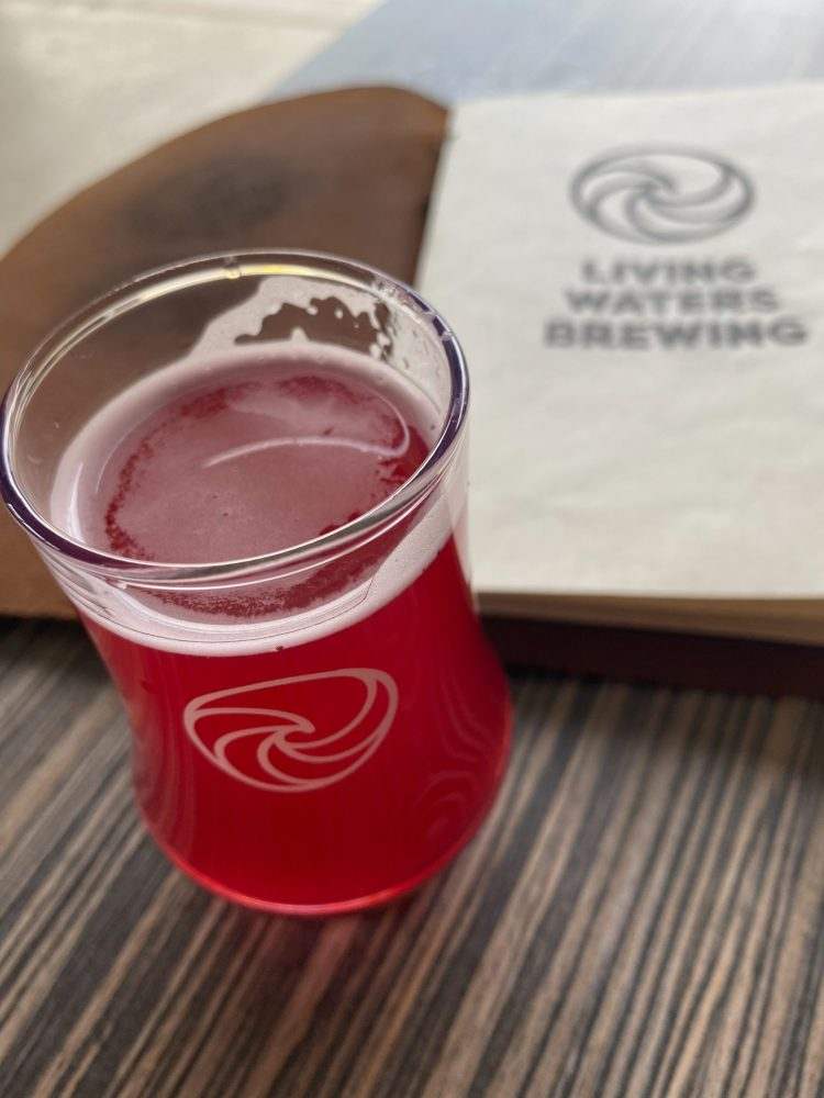 pink glass of beer sitting on the table top with the living waters brewing menu in the background.