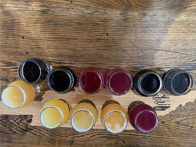 Tennessee shaped flight board holding many yellow, pink and dark brown colored tasting glasses of beer at southern grist brewing.