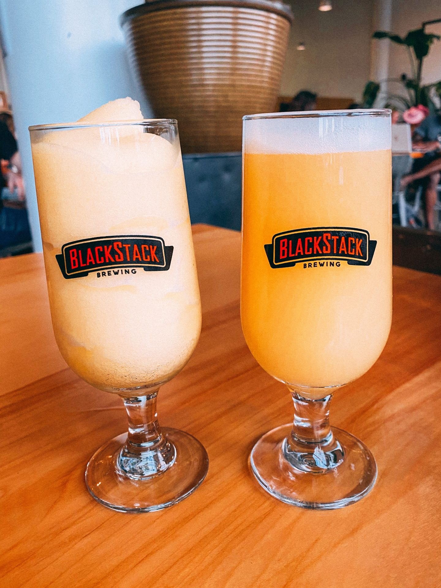 two glasses of beer one with a slushie style beer and another a creamy yellow IPA with the logo Blackstack Brewing at the brewery in St. Paul Minnesota