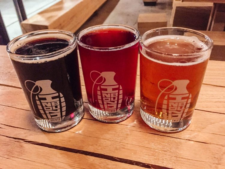 three small glasses of beer sitting on a wooden table top at inbound brewco in minneapolis minnesota during a brewery crawl