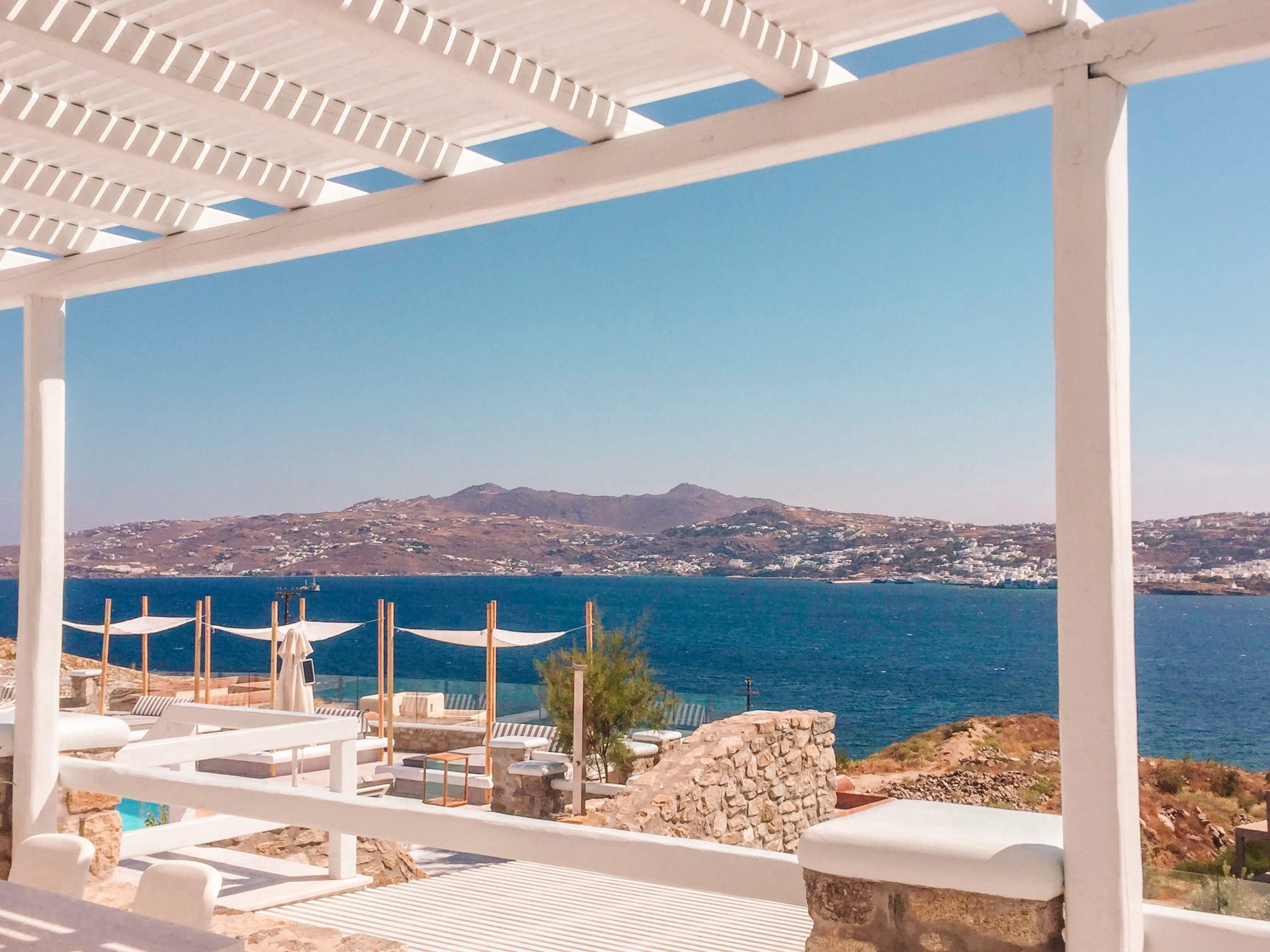 Mykonos No5 hotel with the pool looking out into the ocean and Mykonos town across the bay